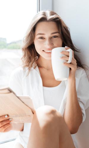 eine Frau, die etwas aus einer Tasse trinkt